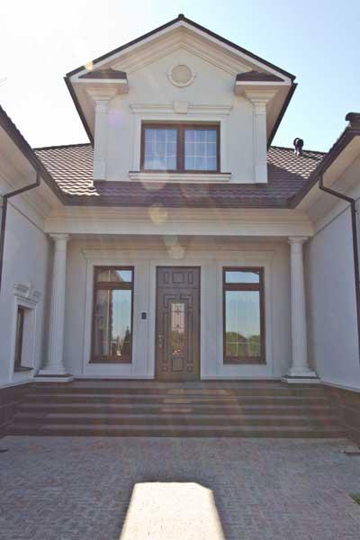 двухэтажный дом, оформленный декоративной лепниной из полиуретана - молдинги, сандрик, колонны, карнизы, вентиляционная решетка, цокольный пояс, классический стиль, в светлых тонах