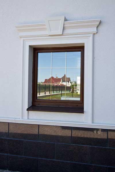окно в обрамлении молдингов, сандрика, замкового камня, декоративная лепнина для оформления окна, украшение окна на фасаде дома, полиуретановая лепнина