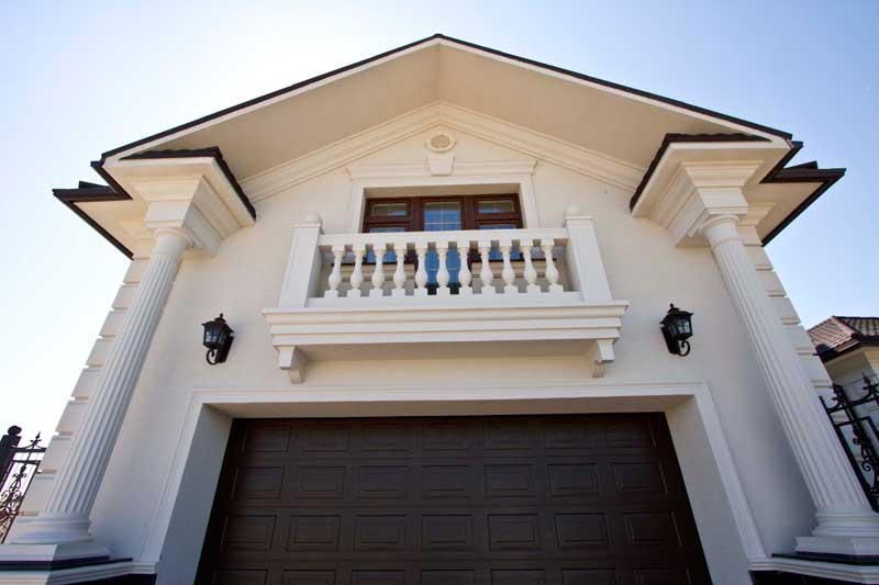 фото балкона с балюстрадой, окно на балкон, оформление пространства под балконом, дизайн балкона, колонны из полиуретана как декоративный элемент, молдинги вокруг въезда в гараж, классический стиль в оформлении дома