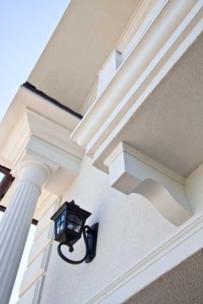 поддерживающие элементы в оформлении фасада - колонны и капитель, балюстрада балкона и консоль, белый цвет во внешнем декоре дома