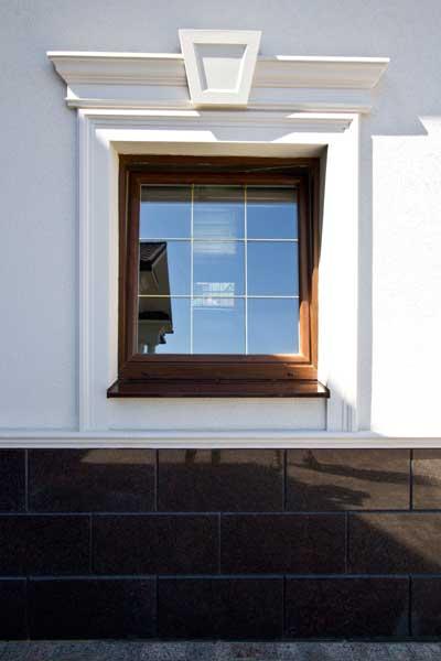 фото окна с молдингом, сандриком с замковым камнем, цокольный карниз под окном, деревянные окна в сочетании с белыми декоративными элементами из полиуретана