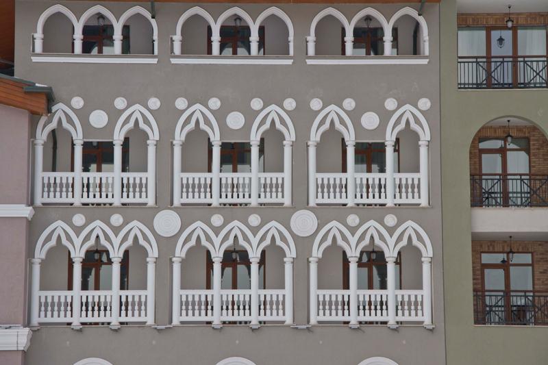 декор лоджий и балконов на фасаде здания, арки и декоративные розетки из полиуретана в декоре балкона