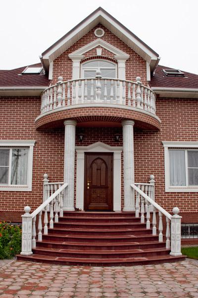 открытый полукруглый балкон с балюстрадой в загородном доме, кирпич и лепнина из полиуретана, белое и красное в оформлении фасада